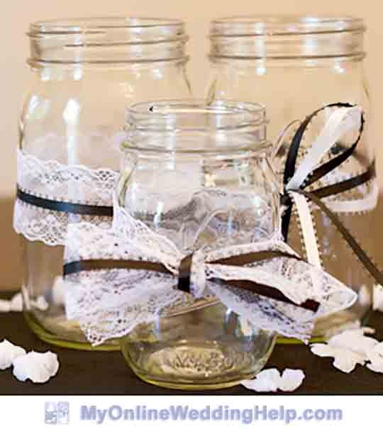Mason jars decorated with ribbon and bows. Makes for nice and easy wedding centerpieces or containers.