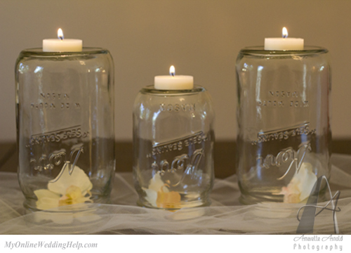 flowers under mason jars, with candles