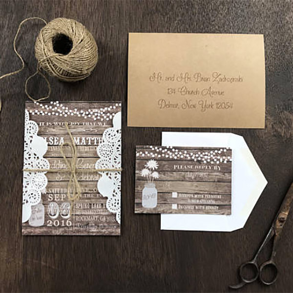 Rustic lace and mason jar wedding invitation. She wraps the invitation in a lace doily and ties with a piece of twine for you. There's a link to purchase in the blog post. Very cute for a country theme or barn wedding. Look under number 5. #RusticWeddingInvitations #MasonJarWedding #WeddingInvitationsIdea #BarnWedding #LaceWeddingInvitation