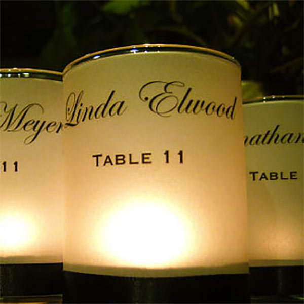 Wedding candle favors with custom votive holder. These are just plain votive candles with a votive wrap around htem. Really inexpensive but elegant looking. There's a link to them in the blog post. Scroll to number 2. #cheapweddingfavors #uniqueweddingfavors #weddingcandlefavors #weddingcandledecor