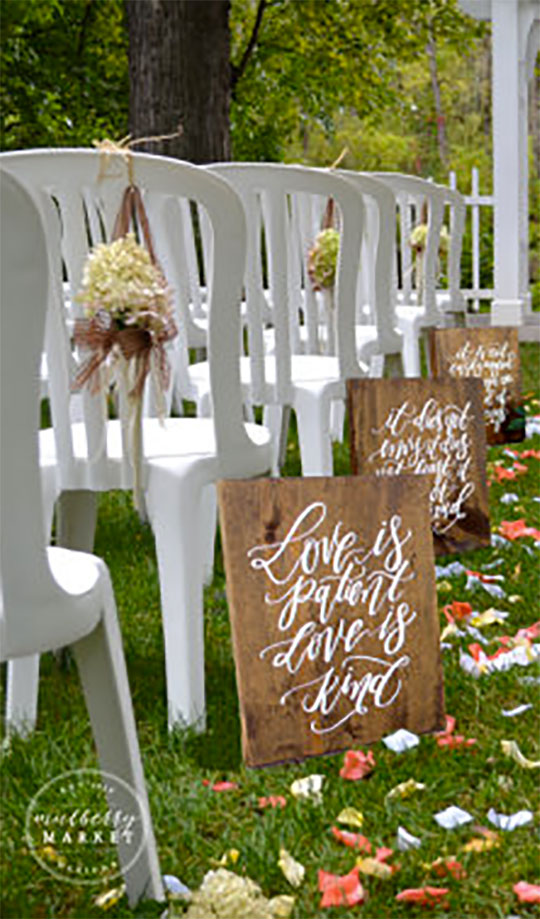 Rustic religious aisle markers with 1 Corinthians 13. Each of these bible verses aisle signs has a passage. The first is Love is patient, love is kind. Scroll to Elegant Country Rustic Wedding Ideas number 10 on the page. #AisleSigns #RusticWedding #CountryWedding #MyOnlineWeddingHelp